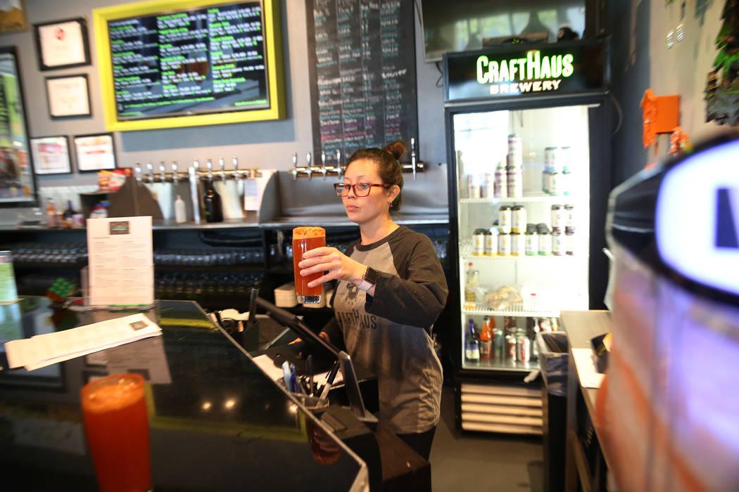 Chelsie Kesjaral, a la derecha, sirve una cerveza para Max Lovelady, en CraftHaus Brewery en He ...