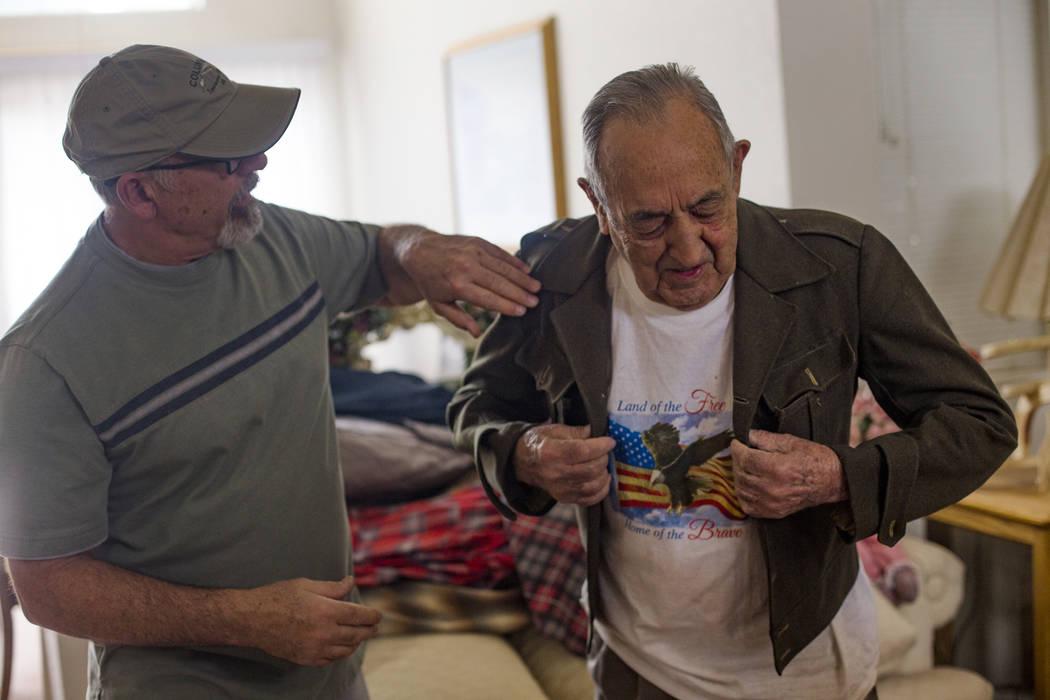"""John Zacari ayuda a su padre Onofrio """"No-No"""" a ponerse su chaqueta cuando estaba en la infanter ..."""
