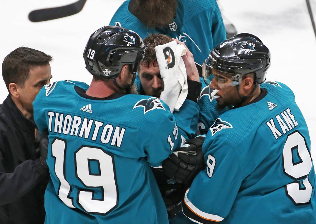 El centro de los Sharks, Joe Pavelski, en medio, recibe ayuda de Evander Kane de su propio equi ...