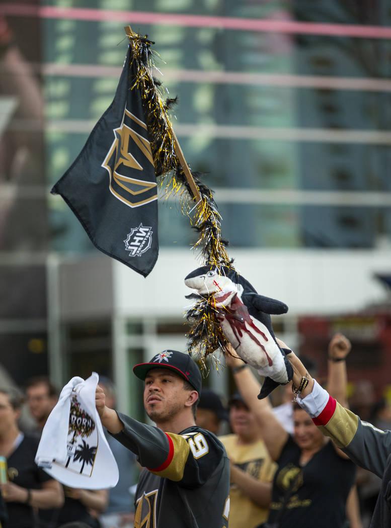 Un fan de los Golden Knights enarbola una bandera con un sangriento tiburón mientras celebra u ...