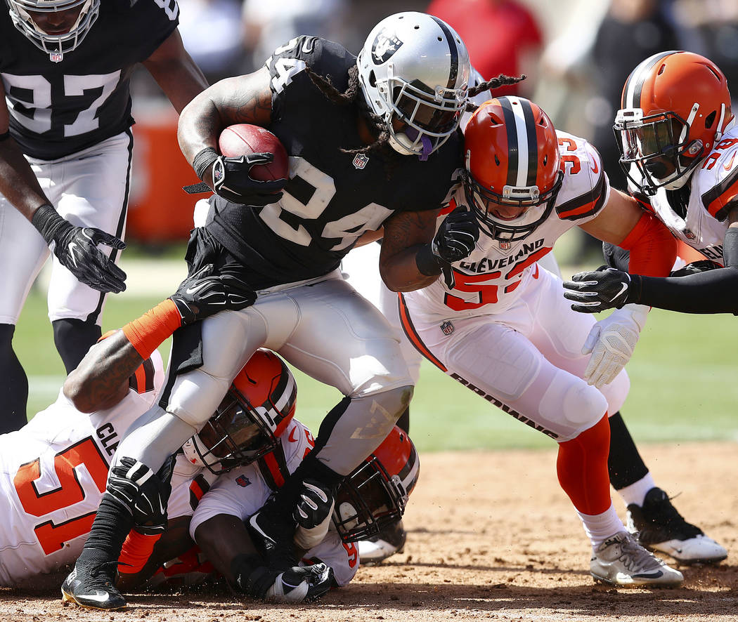 El corredor de los Oakland Raiders, Marshawn Lynch (24), es detenido por los Browns de Clevelan ...