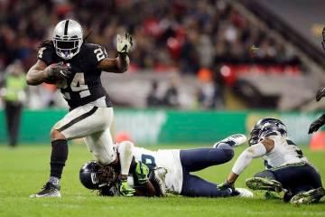 Marshawn Lynch (24), corredor de los Oakland Raiders, es abordado por el esquinero Shaquill Gri ...