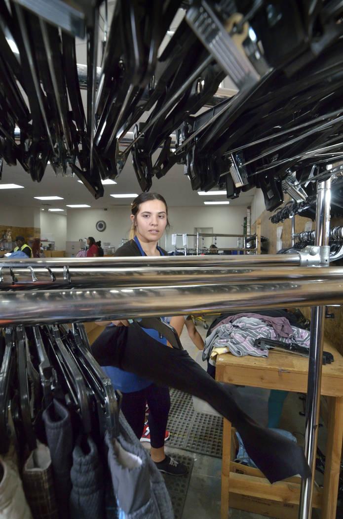 La procesadora de mercancías, Kassandra Van Duyne, cuelga la ropa clasificada en el almacén d ...