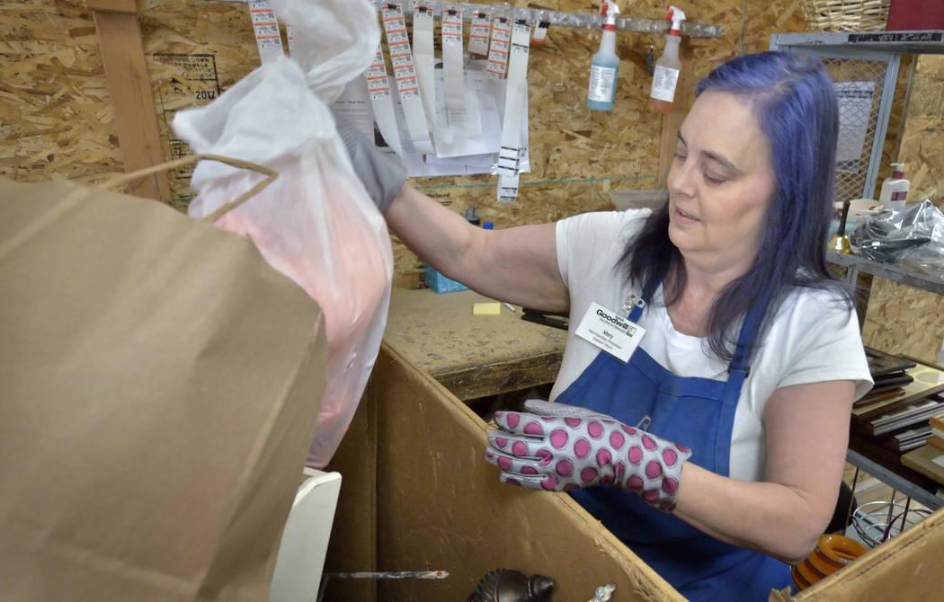 La procesadora de mercancía, Mary Smith, clasifica las donaciones en el almacén de Goodwill T ...