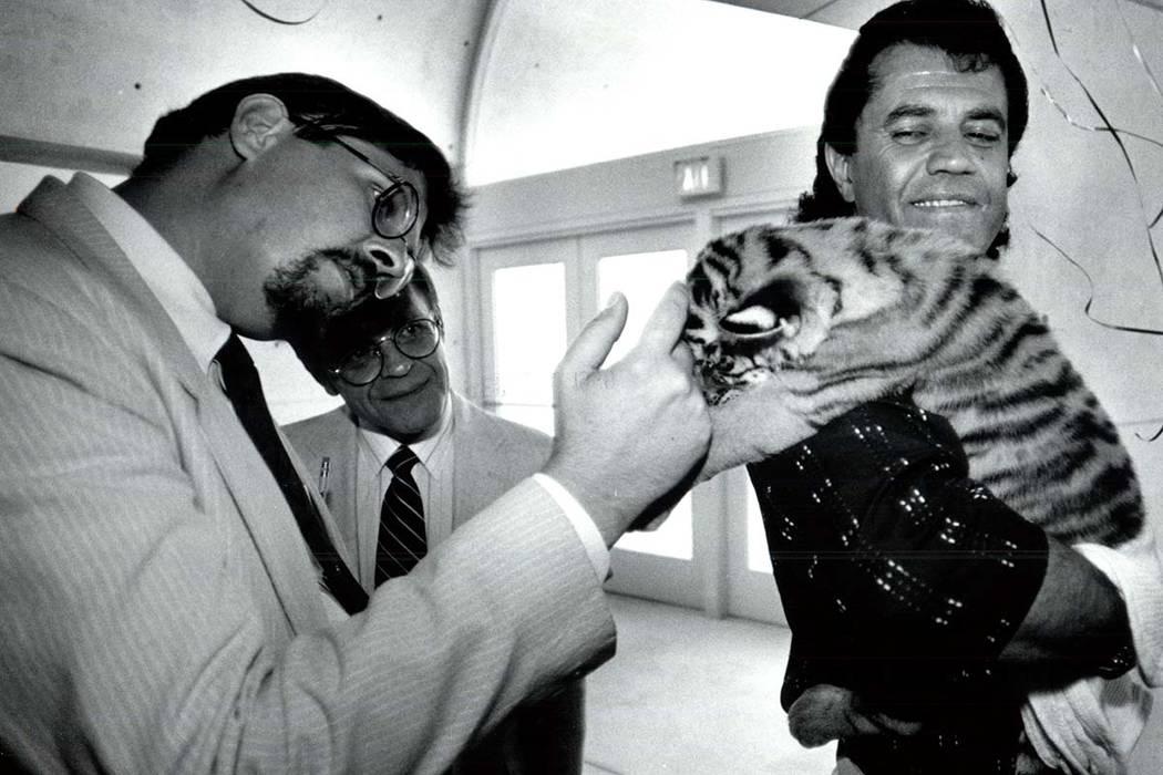 Gary Ogren acaricia a un cachorro de tigre de 4 semanas, Samantha, en manos de Jonathan Kraft e ...