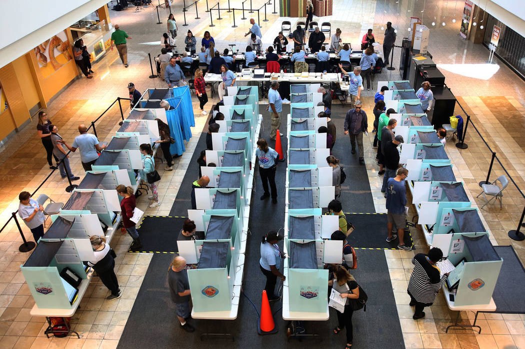Los votantes depositan sus boletas electorales cuando otros se registran en una mesa electoral ...