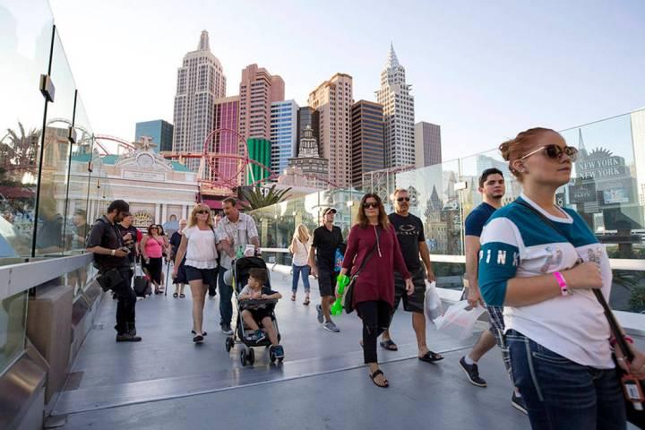 La gente camina por un puente peatonal que une al New York-New York y MGM Grand cerca de la int ...
