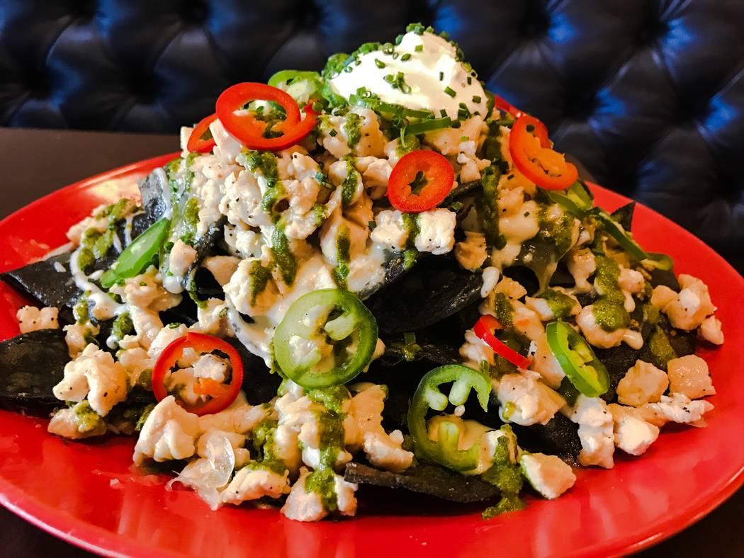 Los Nachos Loco son totopos de tortilla de maíz apilados con trozos de muslo de pollo estofado ...