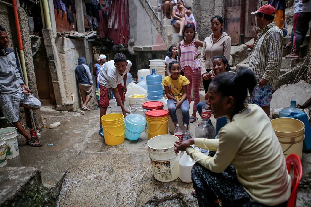 ARCHIVO. Caracas, 11 Mar 2019 (Notimex-dpa).- La gente espera para llenar botes con agua en un ...