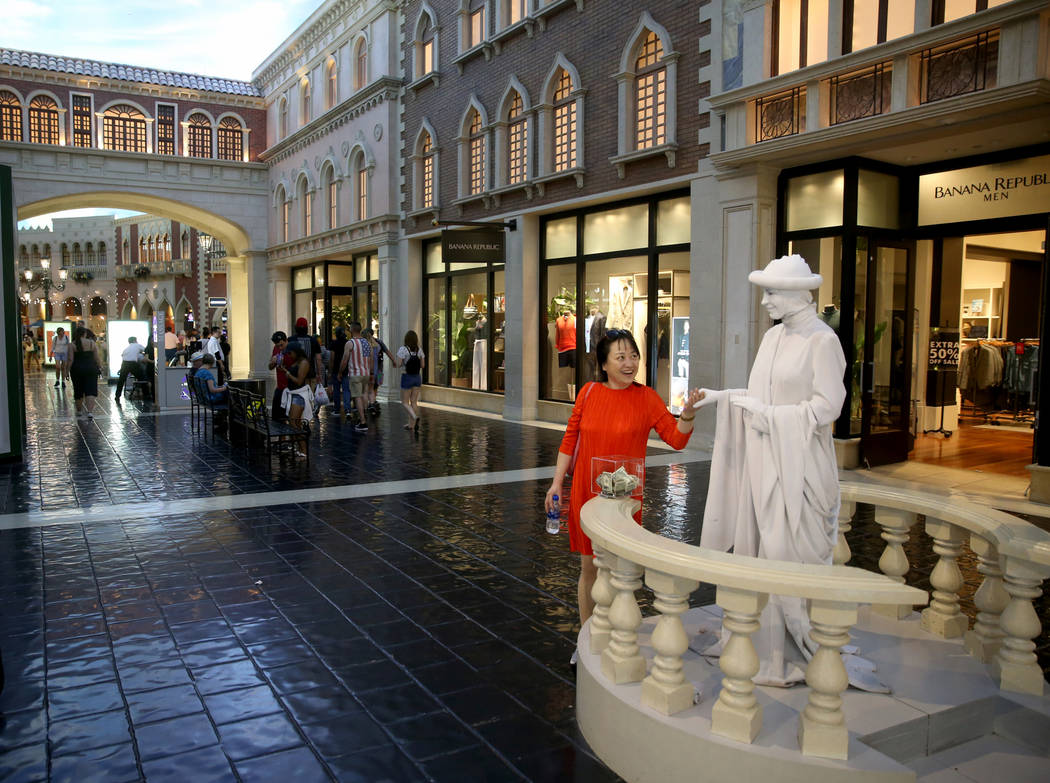 Judy Guo of Canada greets a living statue at The Venetian on the Strip in Las Vegas Thursday, A ...