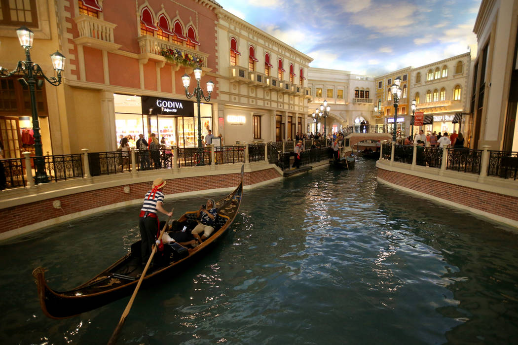 Gondolas float through the Grand Canal Shoppes at The Venetian on the Strip in Las Vegas Thursd ...