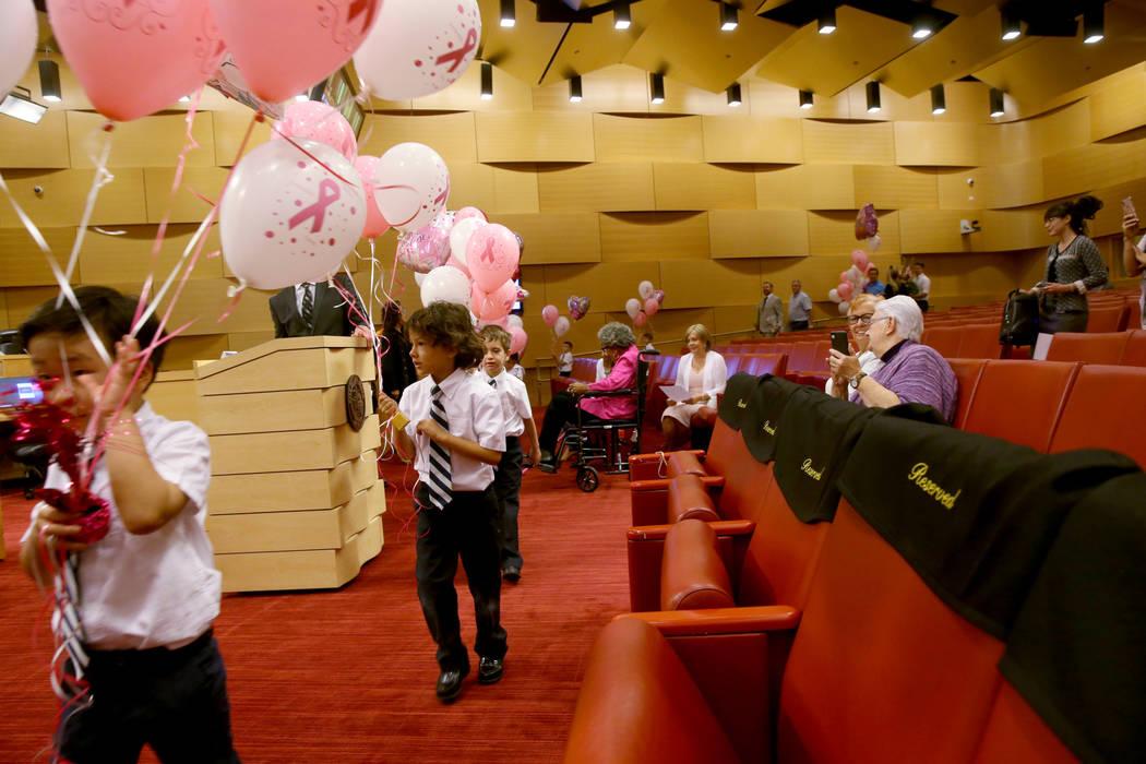 Los niños de kindergarten de The Meadows School, Justin, Nicolás y Owen, entregan globos a la ...