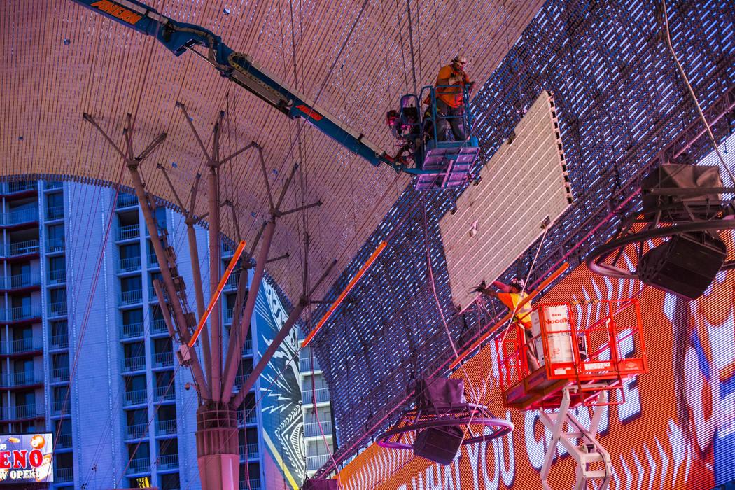 Los trabajadores de la construcción bajan un panel viejo durante el segundo día de renovacion ...