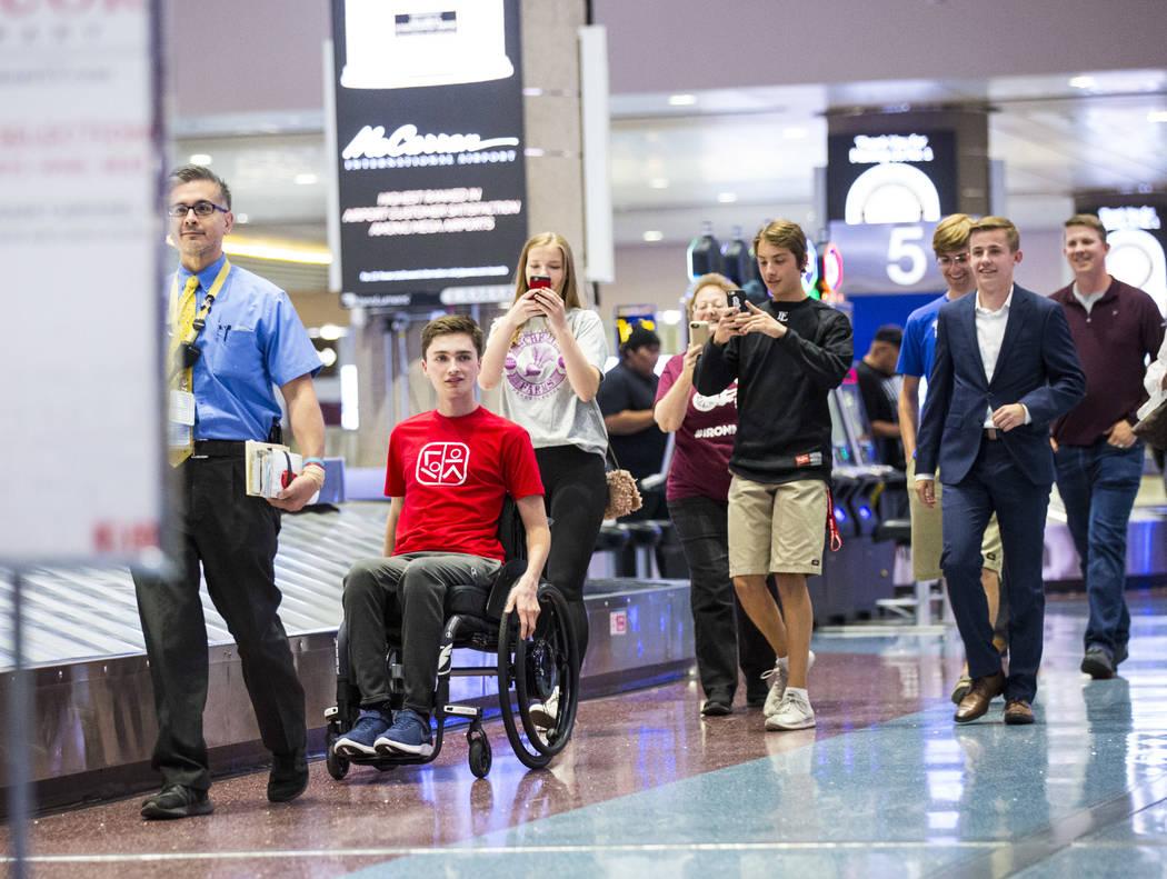 Mark Wilbourne, de rojo, reacciona a una fiesta de bienvenida en el Aeropuerto Internacional Mc ...