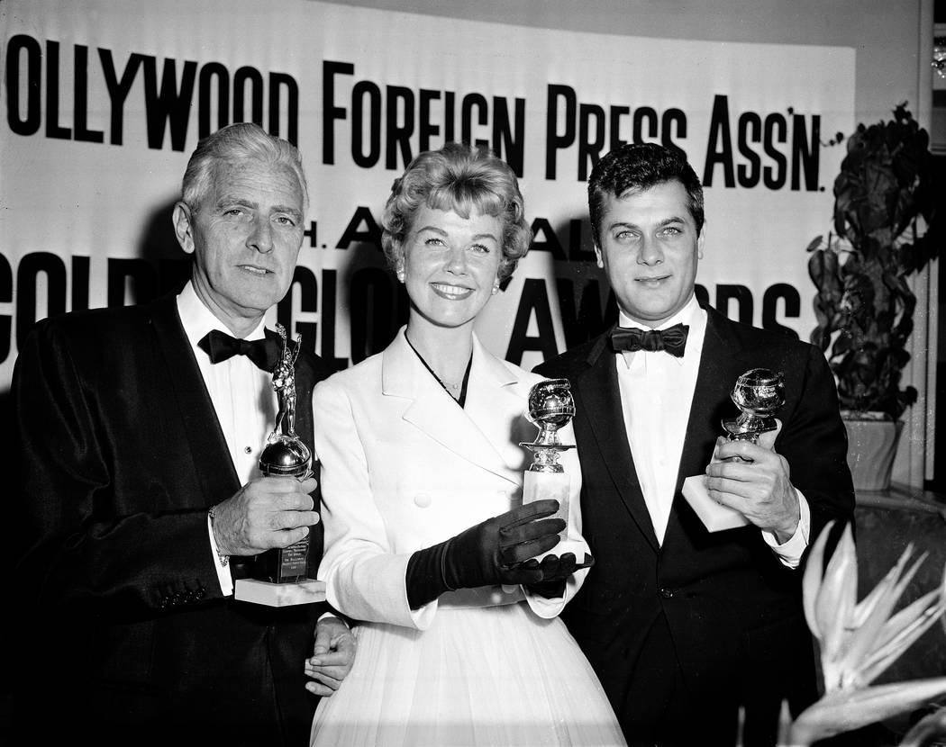 La actriz Doris Day, con Tony Curtis, a la derecha, y Buddy Adler posan con sus premios present ...