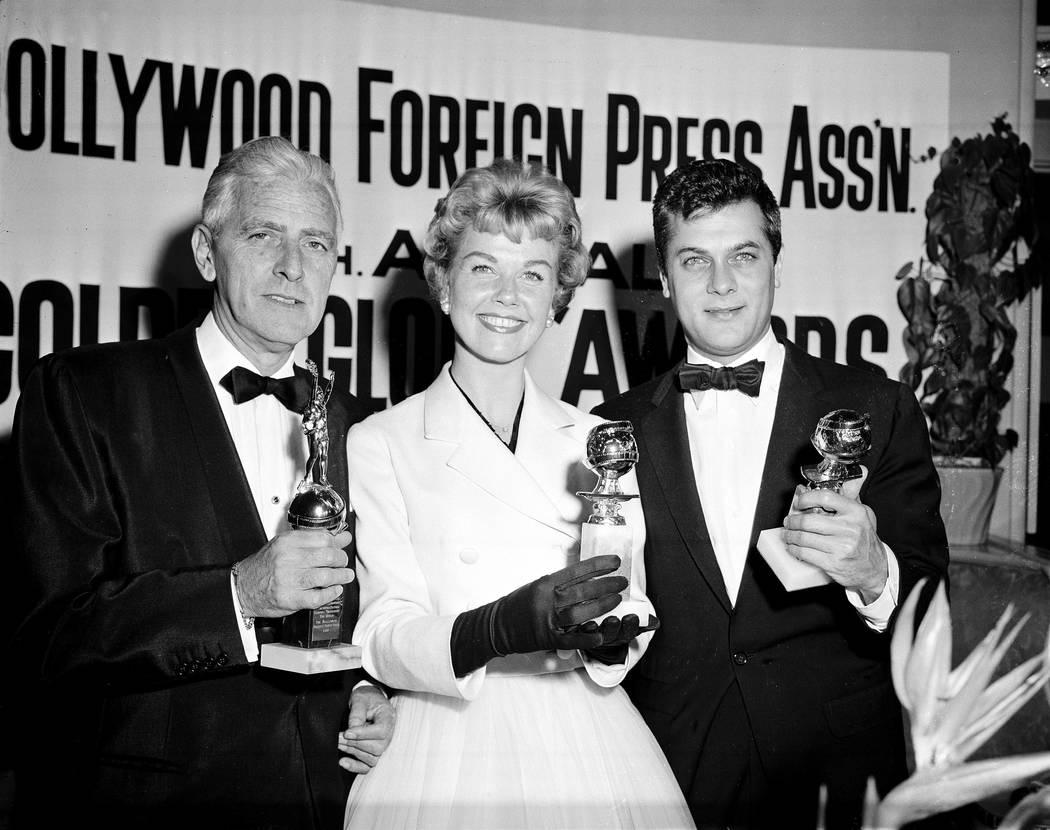 La actriz Doris Day, centro, Tony Curtis, a la derecha, y Buddy Adler posan con sus premios oto ...