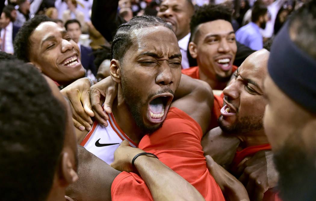 El delantero de los Toronto Raptors, Kawhi Leonard, en el centro, celebra su canasta ganadora d ...