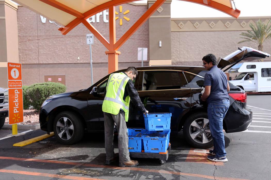 El Asociado de Walmart Dharian H. ayuda a Aditya Subramania, de 17 años, a cargar el pedido en ...