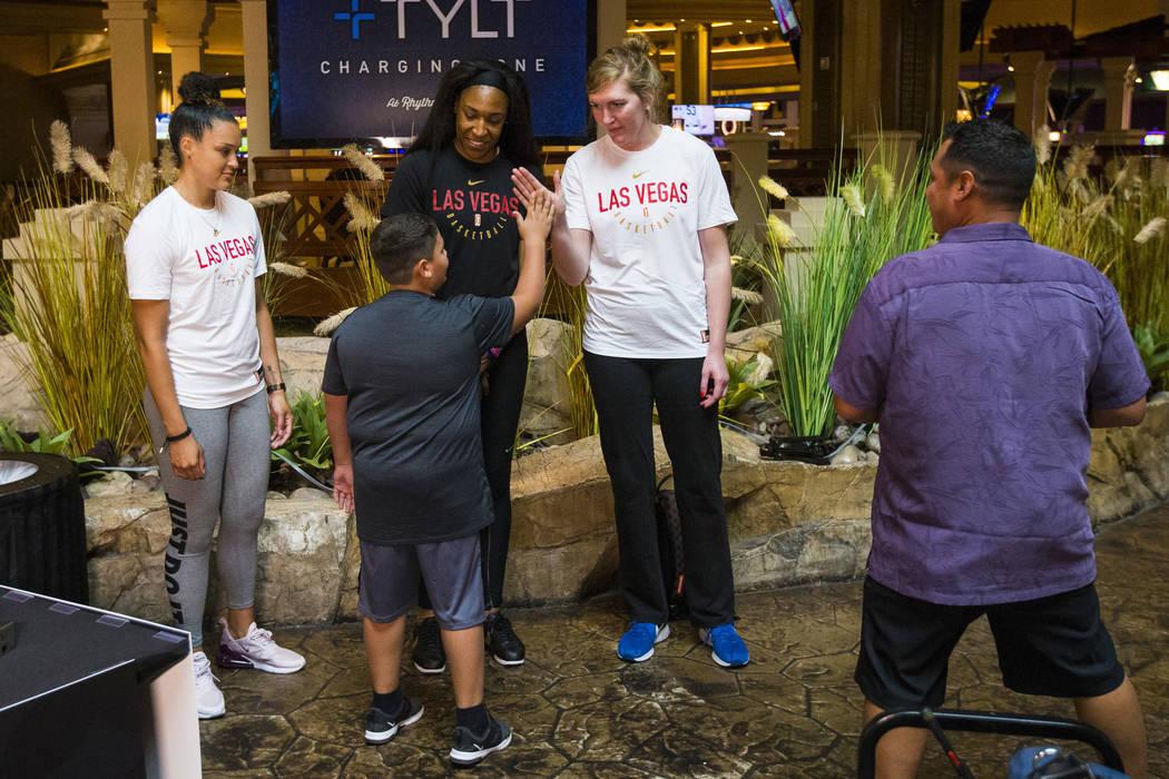 Braeden Sada, de 11 años, choca las palmas con la jugadora Carolyn Swords de Las Vegas Aces, d ...