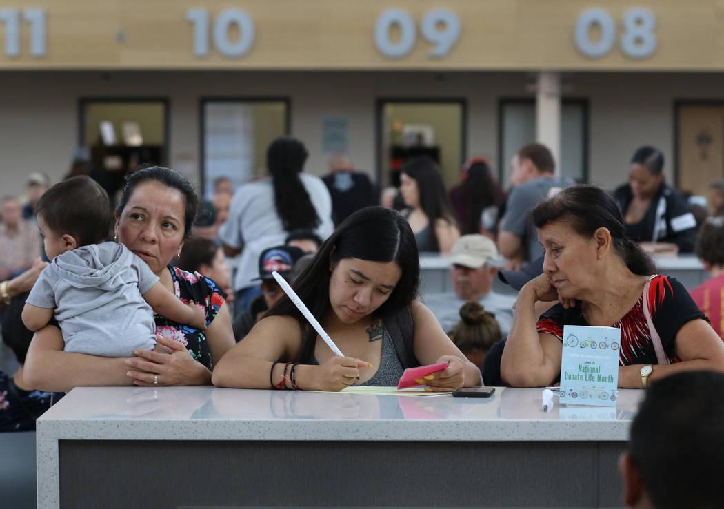 Los clientes, que se negaron a dar sus nombres, llenan los formularios en la oficina del DMV de ...