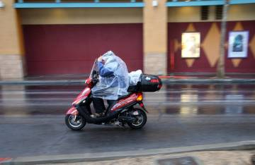 Un conductor de scooter se protege de una lluvia ligera en Las Vegas Boulevard, cerca de Fremon ...