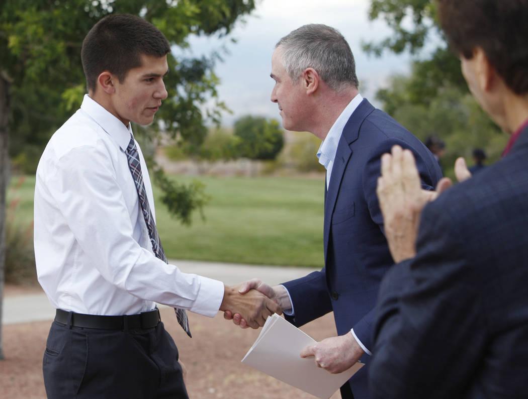 Gabriel Pence, de 17 años, le da la mano a Tom Kovach, el director ejecutivo de la Fundación ...