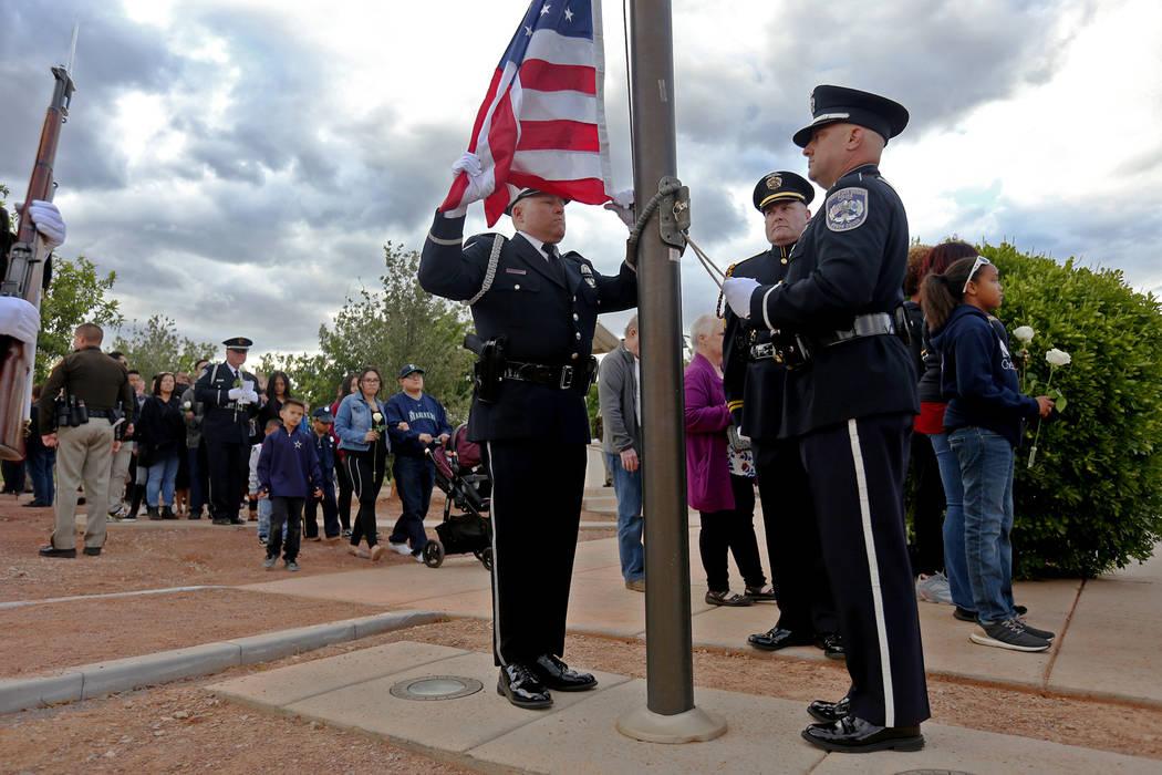 La escolta se prepara para levantar la bandera hasta la mitad del mástil mientras las familias ...