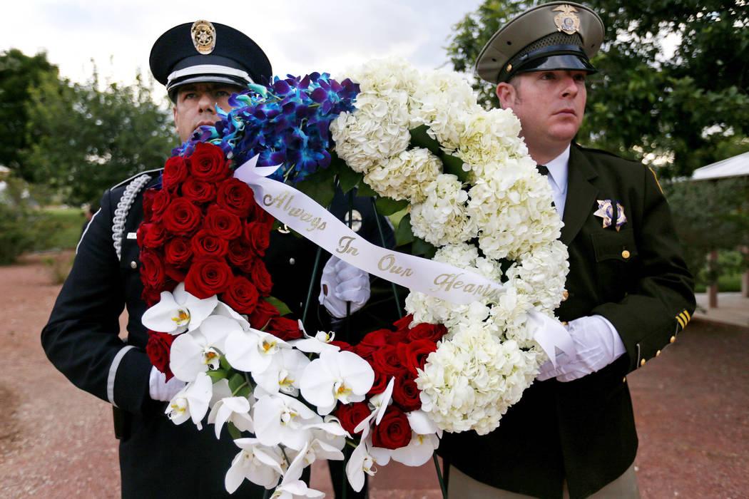 Los oficiales sostienen flores para el servicio conmemorativo de los oficiales de policía del ...
