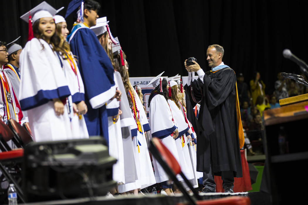 El director de Coronado, Mike Piccininni, a la derecha, toma fotos de los estudiantes, incluido ...