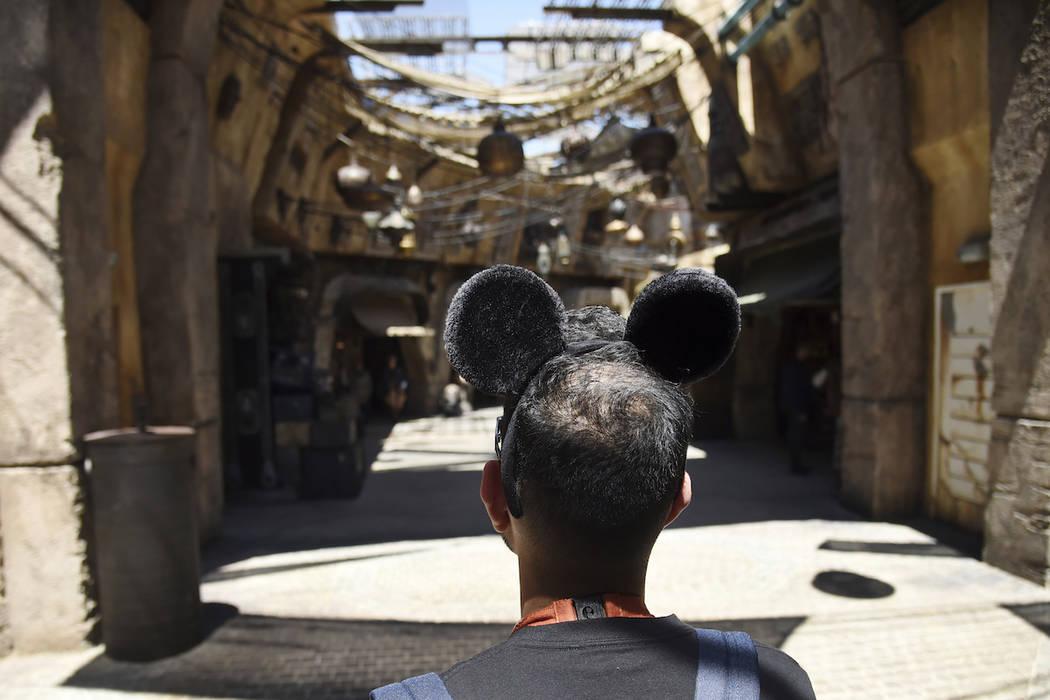 Un visitante mira al mercado en Black Spire Outpost durante Star Wars: Galaxy's Edge Media Prev ...