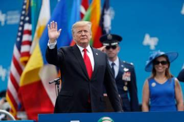 El presidente Donald Trump saluda mientras sube al escenario para hablar en la graduación de l ...
