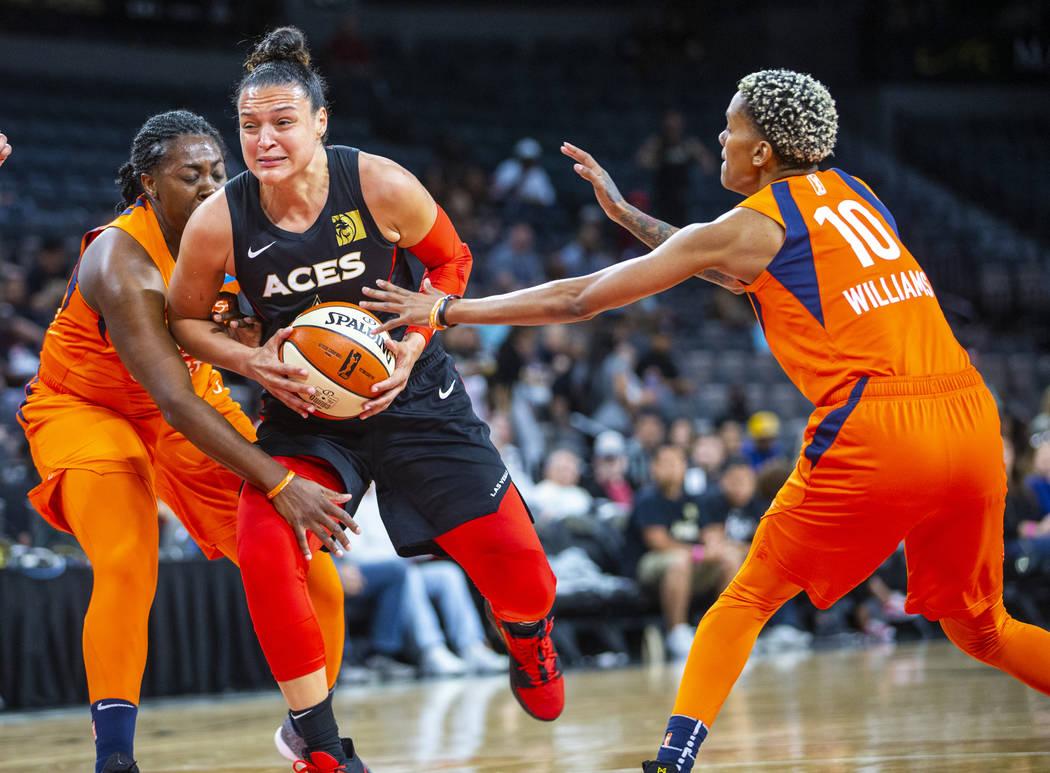La escolta Kayla McBride (21) de las Aces de Las Vegas divide la defensa de la delantera de Con ...