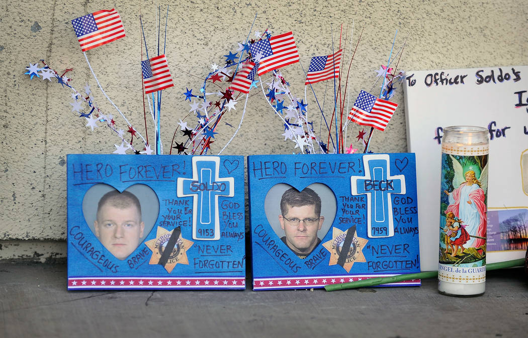 Velas, banderas y otros artículos se sientan en un monumento improvisado cerca de la puerta de ...