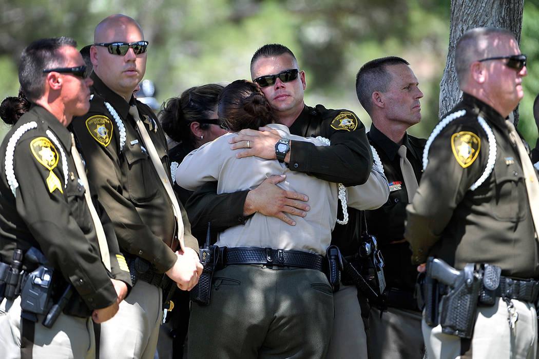 El 12 de junio de 2014, en Las Vegas, los policías de Las Vegas consuelan a cada uno durante u ...