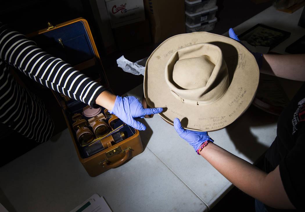 La doctora Paige Figanbaum, a la izquierda, señala un sombrero de vaquero con marcas escritas ...