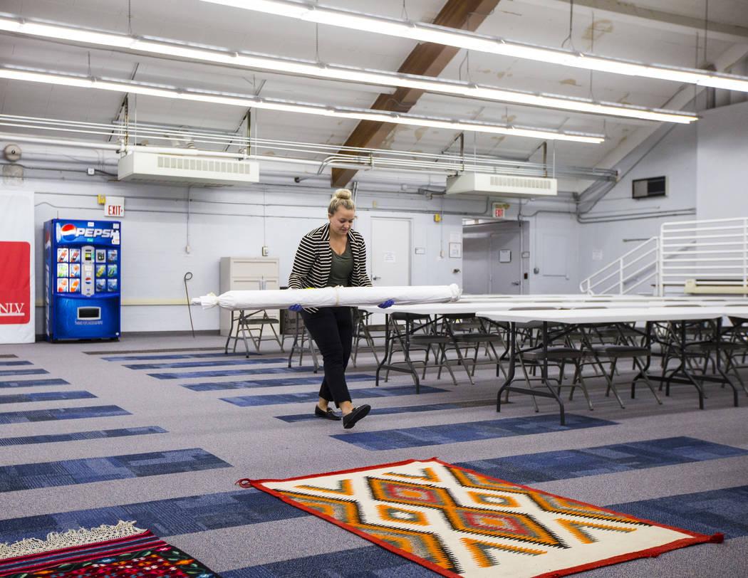 La estudiante de doctorado Paige Figanbaum mueve alfombras y otros artículos de Walking Box Ra ...