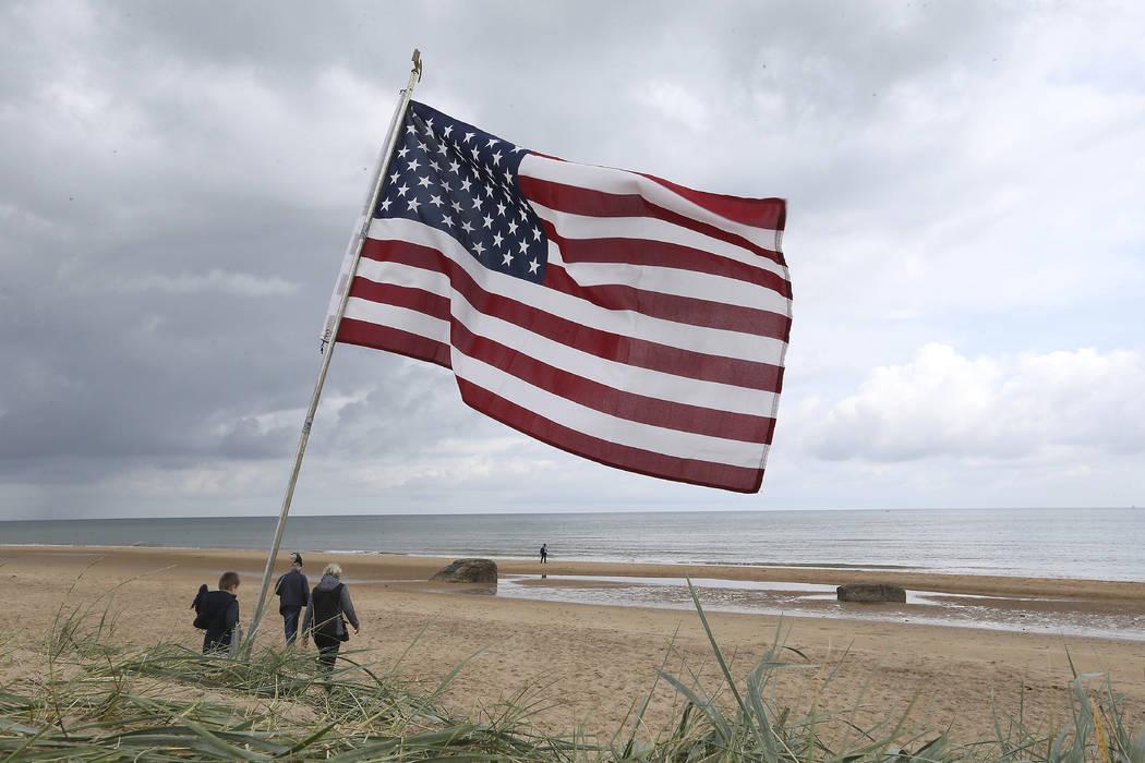 La gente camina por la playa de Omaha, Normandía, Francia, donde se planta una bandera estadou ...