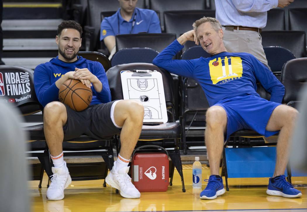 Klay Thompson, de los Warriors de Golden State, a la izquierda, y el entrenador Steve Kerr comp ...
