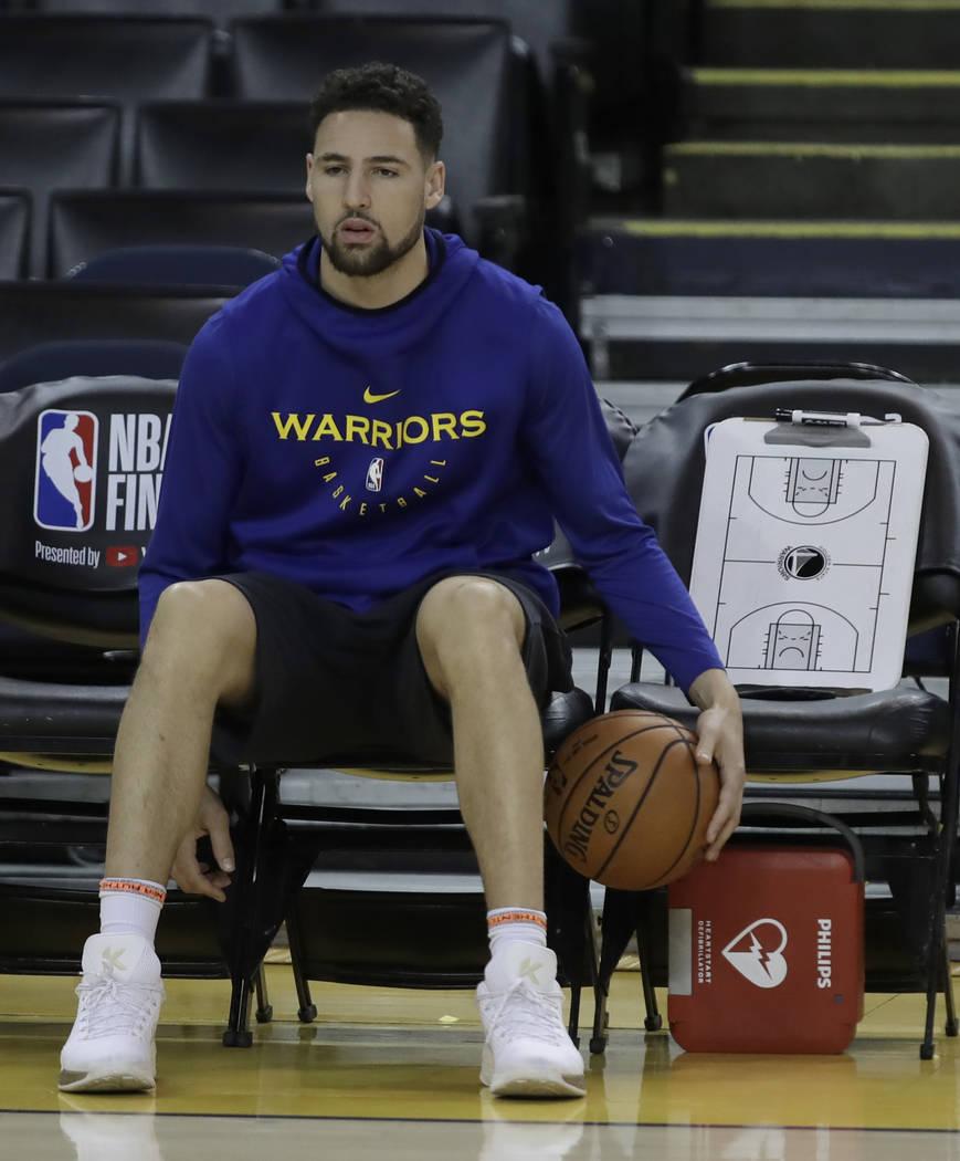 Klay Thompson, de los Golden State Warriors, se sienta en el banco durante la práctica de las ...
