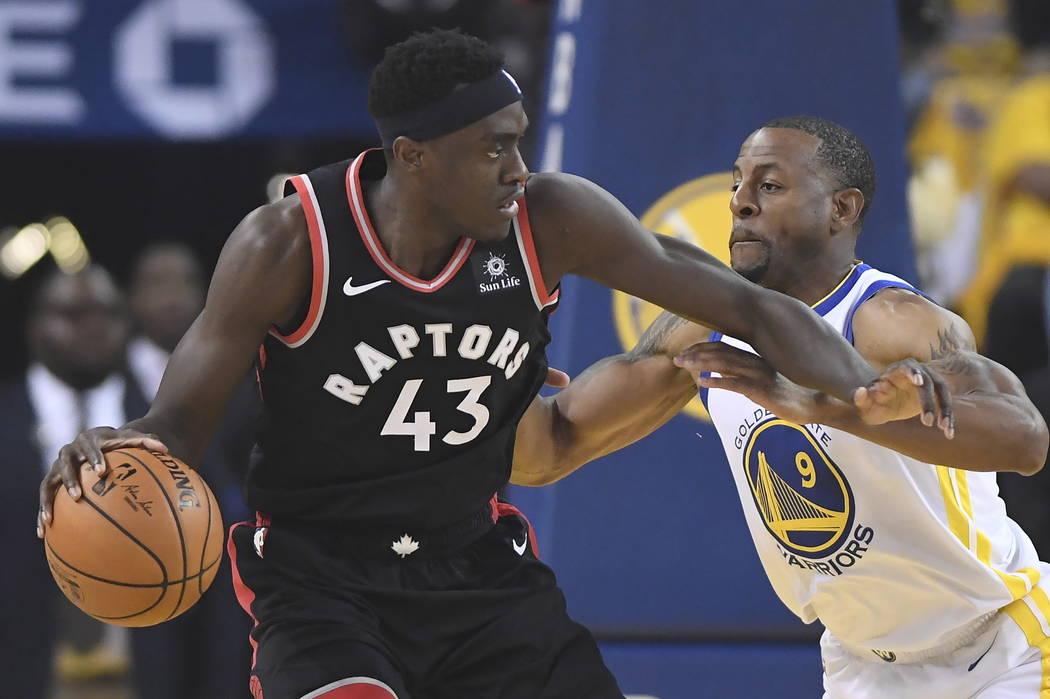 El delantero de los Toronto Raptors, Pascal Siakam (43) retiene al alero de los Golden State Wa ...
