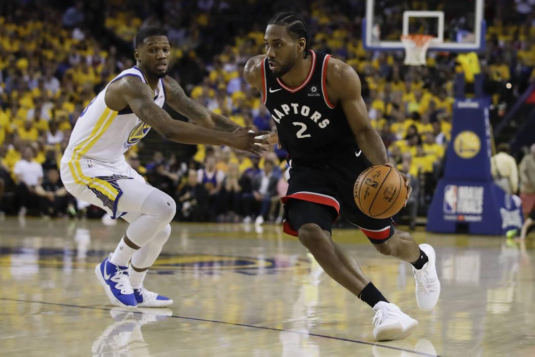 El delantero de los Toronto Raptors Kawhi Leonard (2) dribla contra el delantero de los Golden ...