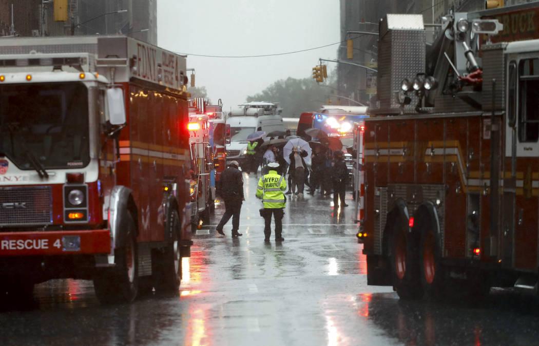 Los socorristas llegan cerca de la escena donde un helicóptero se estrelló en el techo de un ...