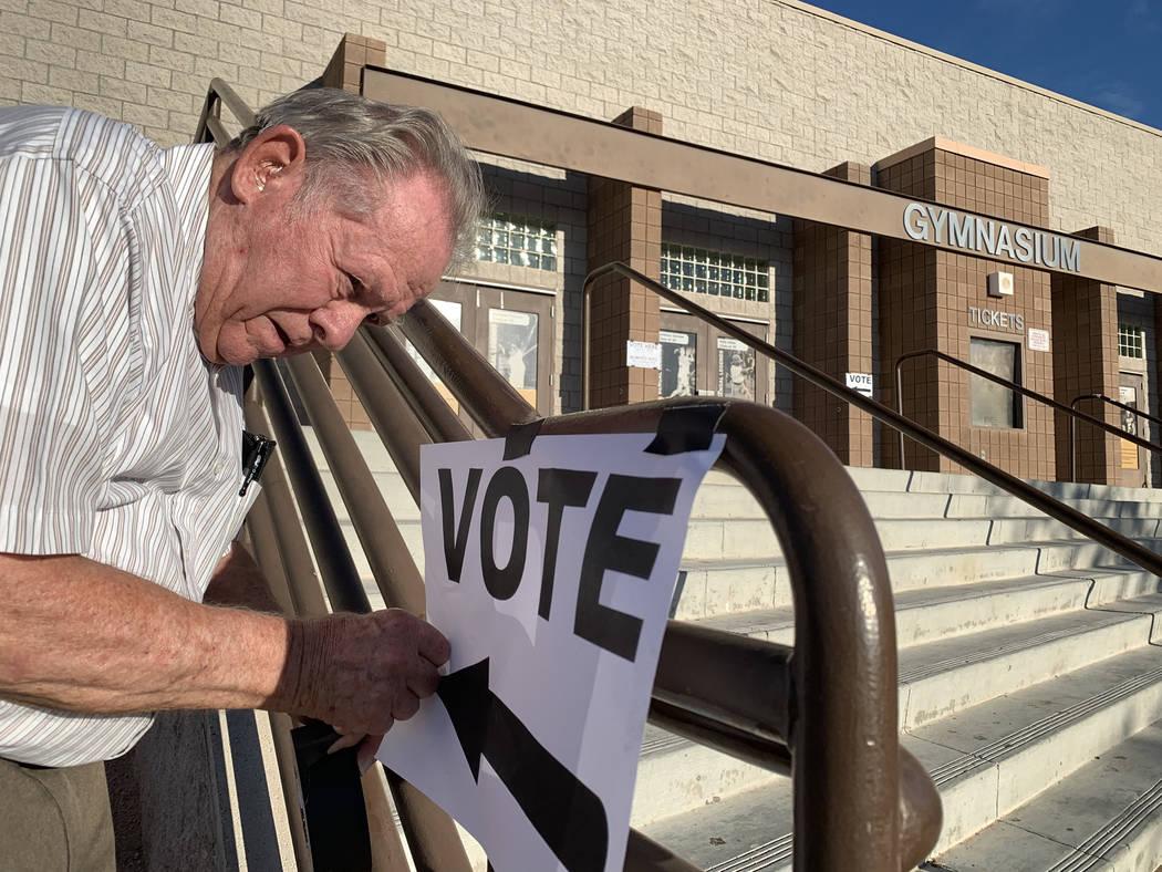 El trabajador electoral Donald Somerville pega un cartel para las elecciones municipales en Bon ...