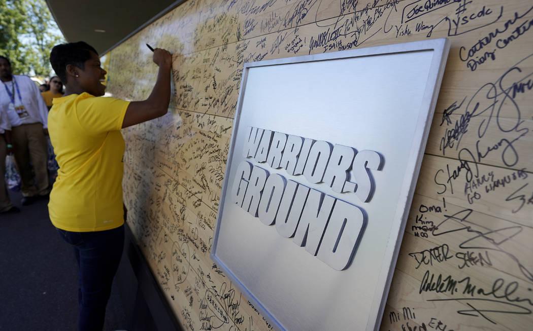 Un fan de los Golden State Warriors firma una vieja pieza del piso de baloncesto fuera del Orac ...