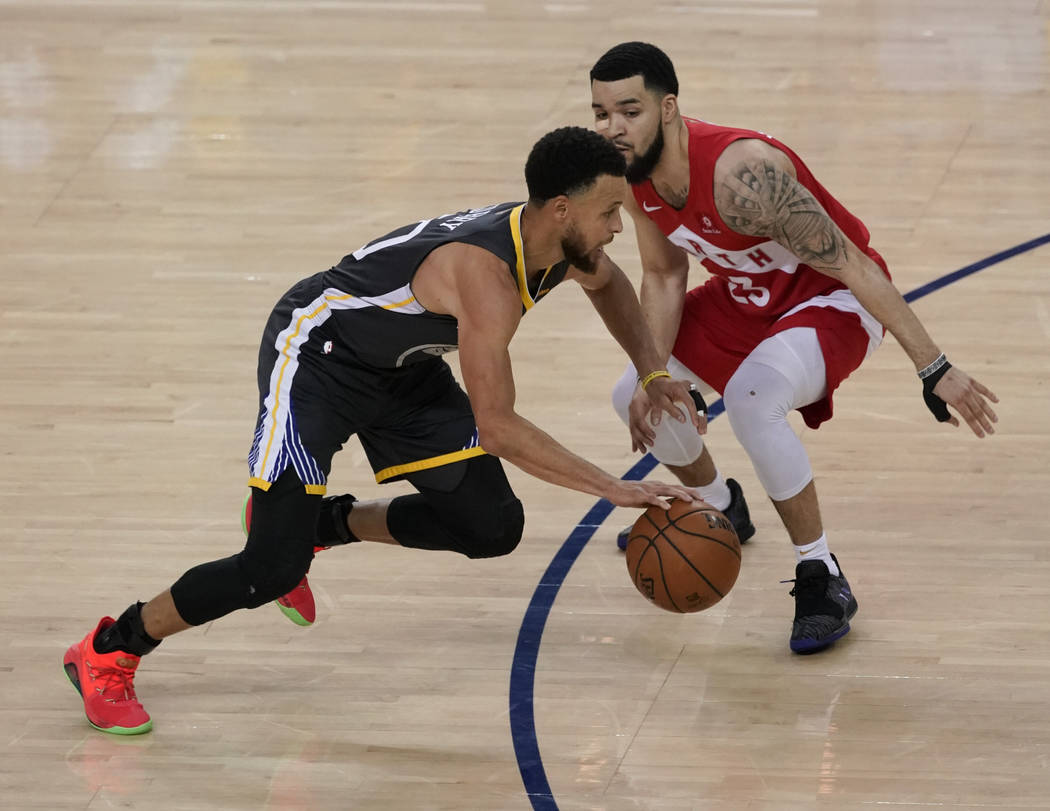 El guardia de los Golden State Warriors, Stephen Curry, a la izquierda, dribla contra el escolt ...