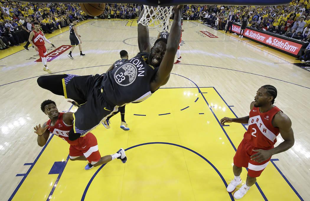 El delantero de los Golden State Warriors, Draymond Green (23), lanza sobre el escolta de los T ...