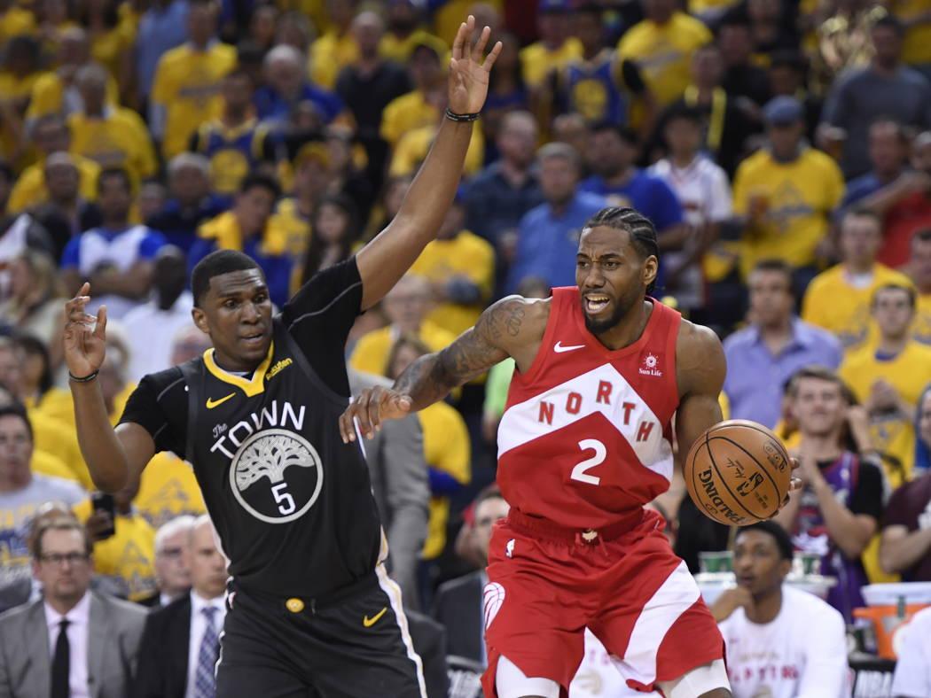 El delantero de los Toronto Raptors Kawhi Leonard (2) pasa por el centro de Golden State Warrio ...