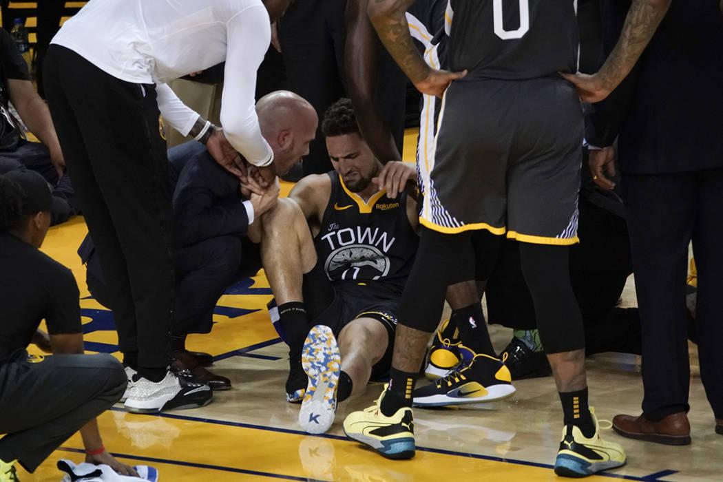 El guardia de los Golden State Warriors, Klay Thompson, en el centro, recibe ayuda luego de suf ...