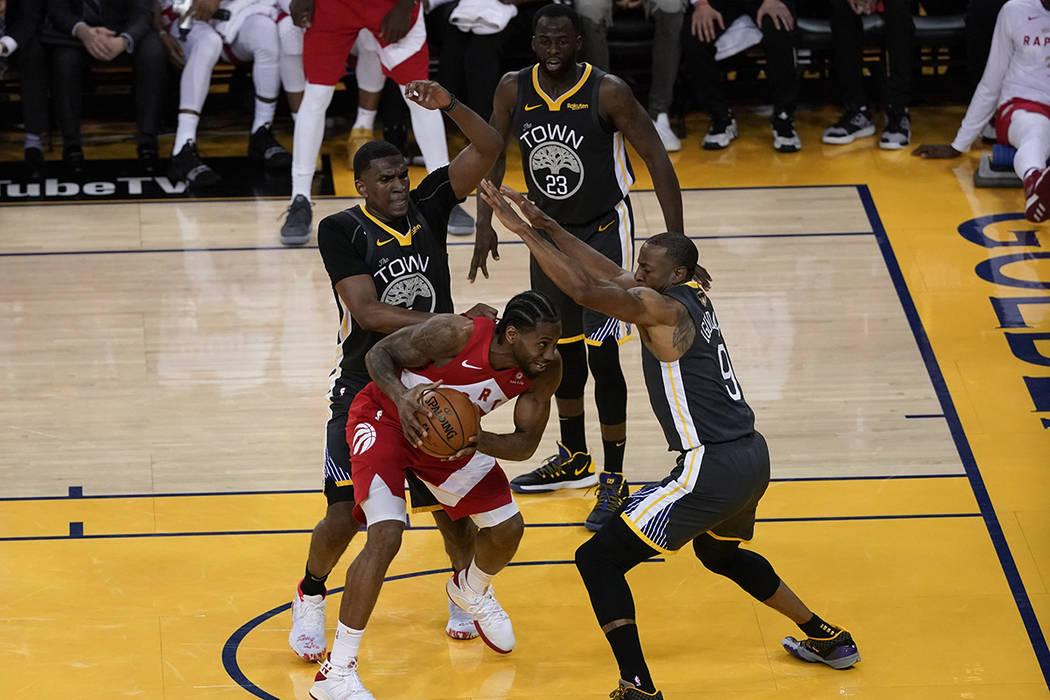 El delantero de los Toronto Raptors, Kawhi Leonard, es atacado por el centro de los Golden Stat ...