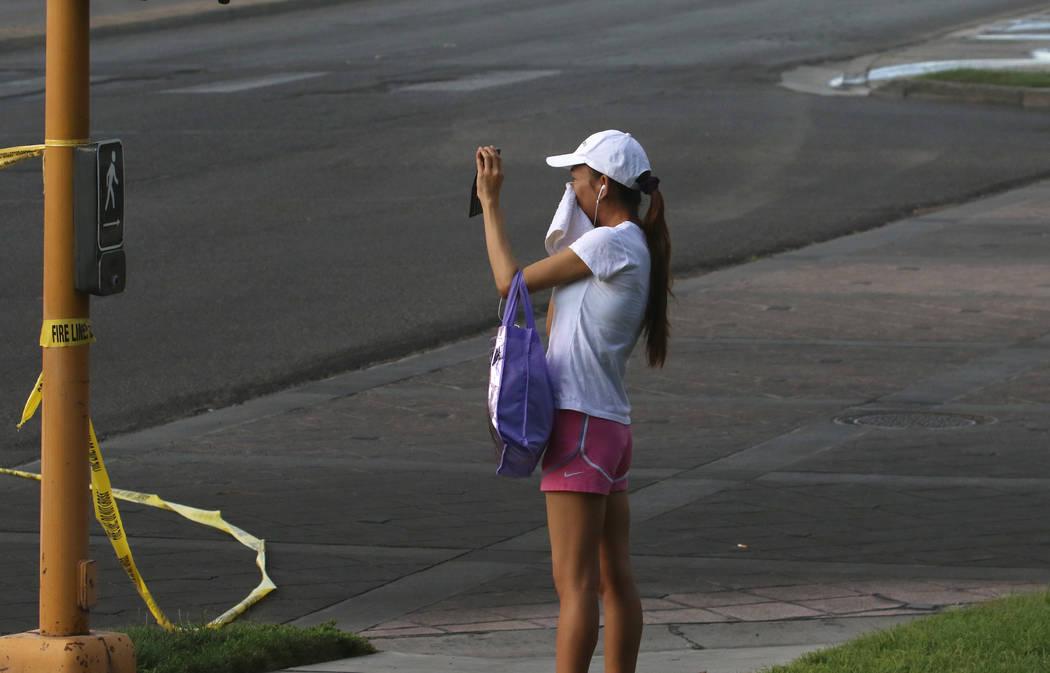 Una mujer se cubre la cara para protegerse del humo mientras toma una foto en The Park 3900 en ...